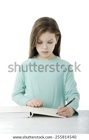 Little girl at the table in school isolated on white - stock photo