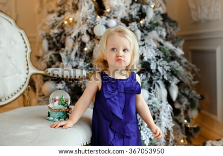 Little girl baby blonde in a blue dress with displeasure pouted on the background of Christmas decorations - stock photo