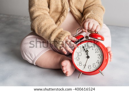 Little girl baby child holding red alarm clock. New Year's clock at midnight. Twelve O'clock midnight in retro style. Christmas decoration on wood background. a clock displays just before New Year