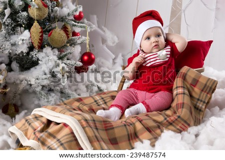 Little girl, baby sitting on sleigh of Santa Claus in Christmas interior - stock photo