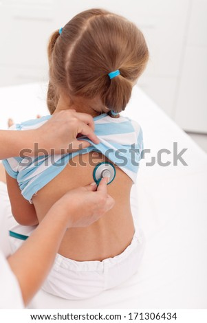 Little girl back being examined with stethoscope at the doctor office - stock photo