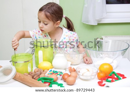 little girl bakeing in the kitchen - stock photo