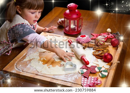 Little girl baking Christmas cookies cutting pastry with a cookie cutter  - stock photo