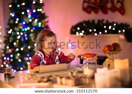 Little girl baking Christmas pastry. Children bake gingerbread. Toddler child preparing cookie for family dinner on Xmas eve. Decorated kitchen or dining room with fireplace, tree, candles and lights - stock photo