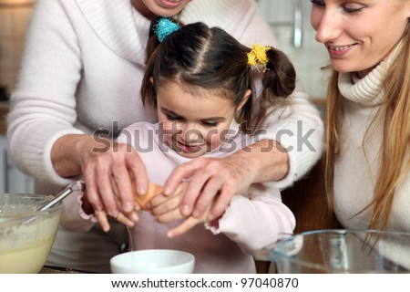 Little girl baking with her family - stock photo