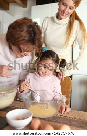 Little girl baking with her mother and grandma - stock photo