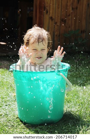 Little girl bathes in a bucket in the yard