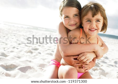 Little girl being hugged by her sister on sandy beach - stock photo