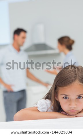 Little girl being sad while parents are quarreling in the kitchen - stock photo
