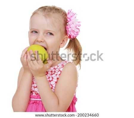 little girl biting a big yellow apple on white background