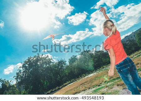 little girl blonde in jeans and a red jacket standing on the street and starts a kite, looking at the sun.