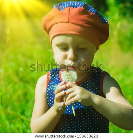 Little girl blowing a dandelion in the sunlight. - stock photo