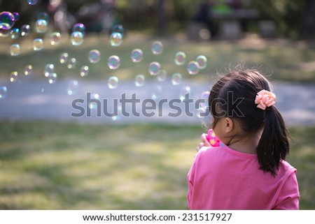 Little girl blowing bubbles under the sun