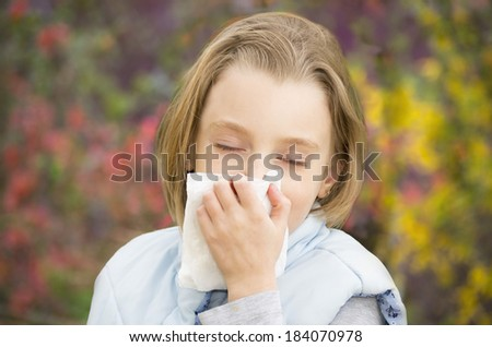 Little girl blowing her nose. Allergic to flowers in early spring. - stock photo