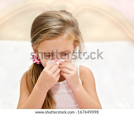 Little girl blowing her nose in a great effort closeup - stock photo