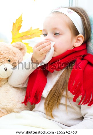 little girl blowing her nose while sitting on the window - stock photo