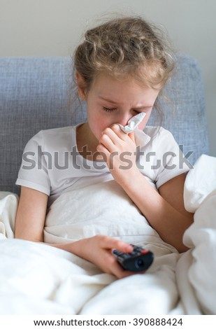 Little girl blowing her nose while watching TV at home. - stock photo