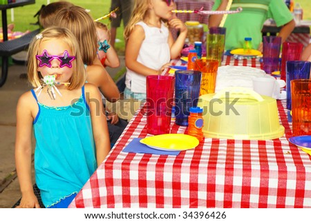 Little girl blowing paper party horn at a birthday party - stock photo