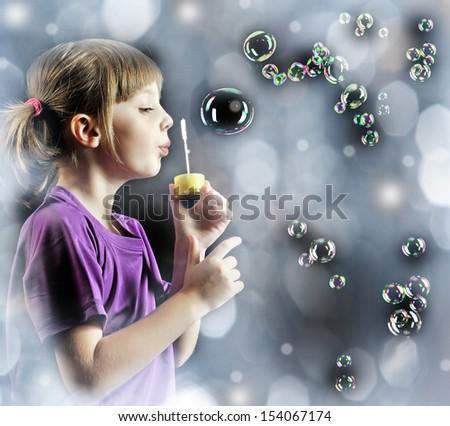 little girl blowing soap bubbles - stock photo