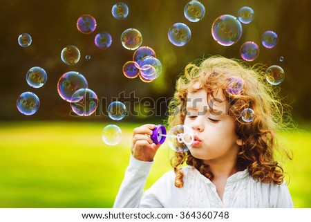 little girl blowing soap bubbles in summer park. Background toning for instagram filter. - stock photo