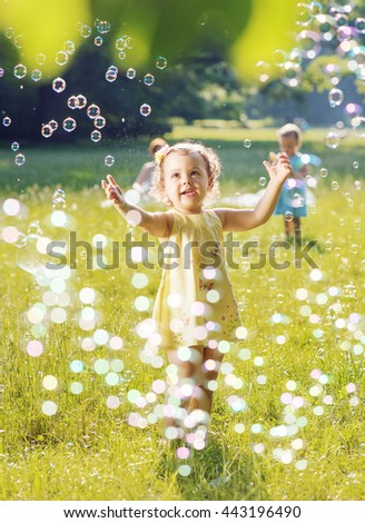 Little girl blowing soap bubbles on a summer meadow - stock photo