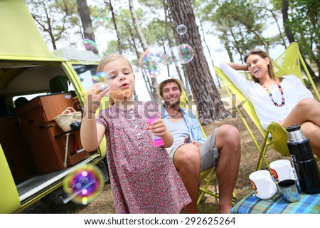 Little girl blowing soap bubbles, parents in background