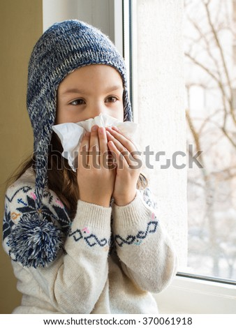 Little girl blows his nose in a paper tissue - stock photo