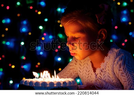 little girl blows out the candles on the cake - stock photo