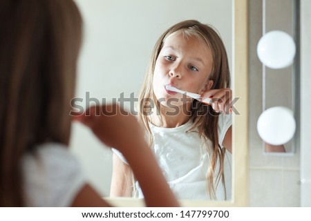 Little girl brushes teeth in the bathroom - stock photo