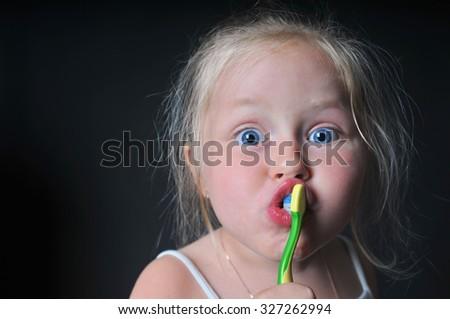 little girl brushing her teeth, girl brushing her teeth, funny little girl brushing her teeth, dark background - stock photo
