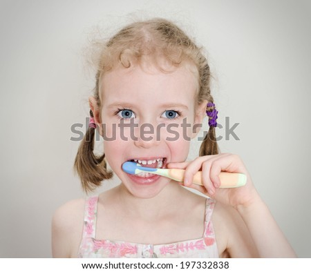 Little girl brushing her teeth with toothbrush. - stock photo