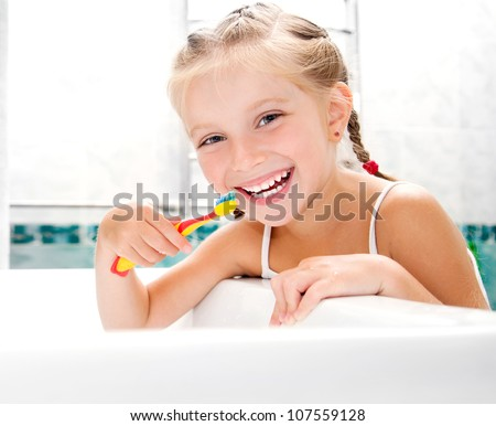 Little girl brushing teeth in bath - stock photo