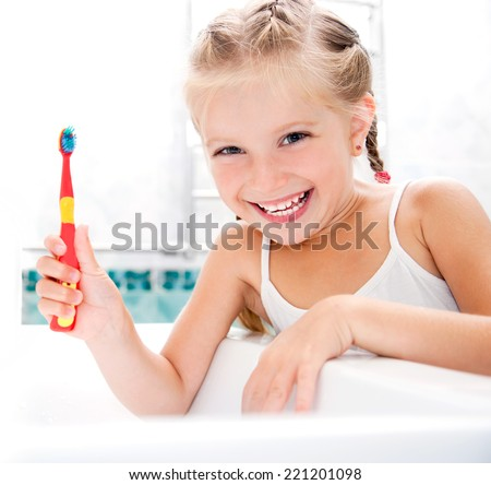 Little girl brushing teeth in bath - stock photo
