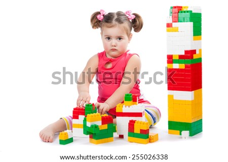 little girl builds a tower isolation on white - stock photo