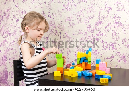 little girl builds bricks at the table