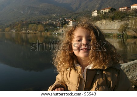 little girl by the lake in a winter sunny light