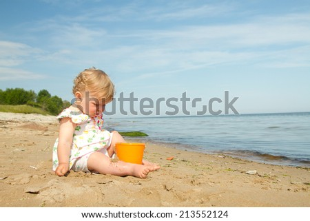 little girl by the sea. child he played in the sand. one year