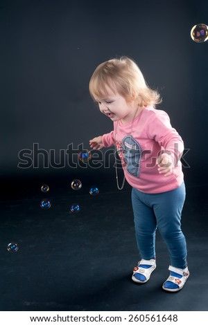 Little girl catches soap bubbles over black background - stock photo