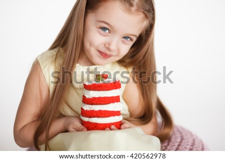Little girl celebrating a birthday with a  small red velvet cake. Cute blond preschooler holding beautiful tasty cake with strawberry - stock photo