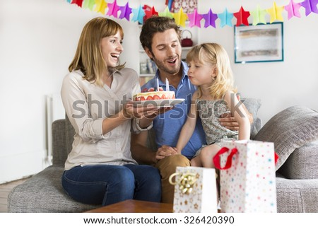 Little girl celebrating birthday party in modern white house. She blows the candles - stock photo