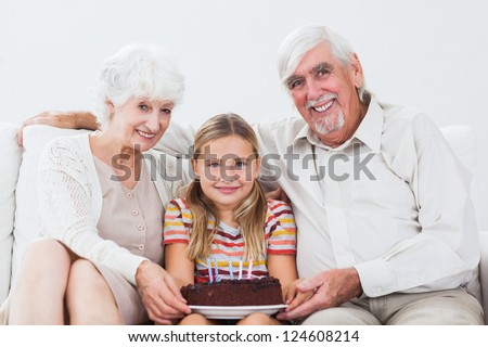 Little girl celebrating birthday with grandparents with cake on the couch