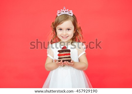 Little girl celebrating with her birthday cake. Preschooler kid wearing white princess dress holding mini cake over red background - stock photo