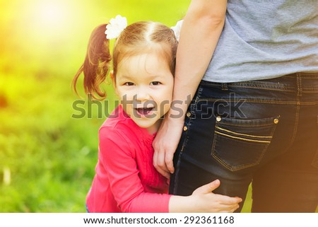Little girl cheerfully hugging leg of mother. Mom and child having fun outdoors. Happy family portrait at sunny background  - stock photo