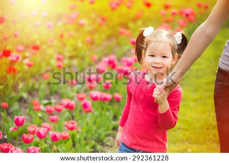 Little girl cheerfully walking in summer urban park holding hand of mother. Mom and child having fun outdoors. Happy family portrait at flowers background.  - stock photo