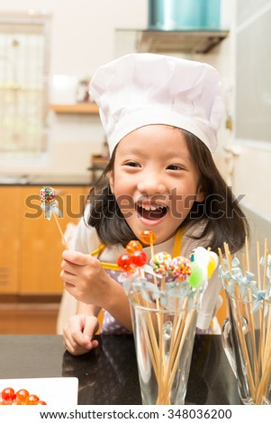 Little girl chef enjoy making jelly candy in kitchen