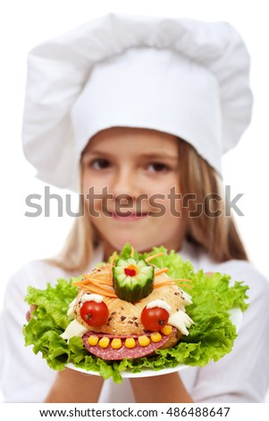 Little girl chef holding creative sandwich, closeup - food with character