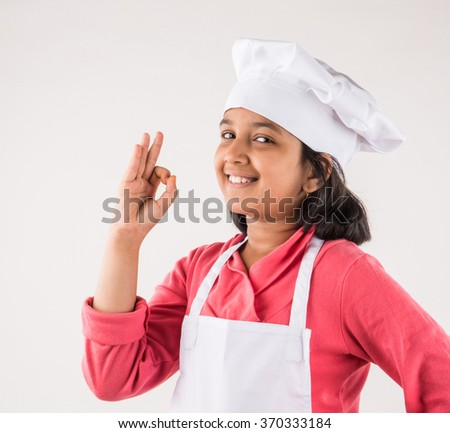 little girl chef showing ok sign, - stock photo
