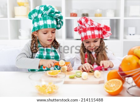 Little girl chefs in the kitchen - slicing fruits for a salad - stock photo