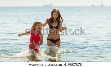 Little girl child and mother having fun in ocean. Kid and woman bathing in sea splashing water. Summer vacation holiday relax. - stock photo