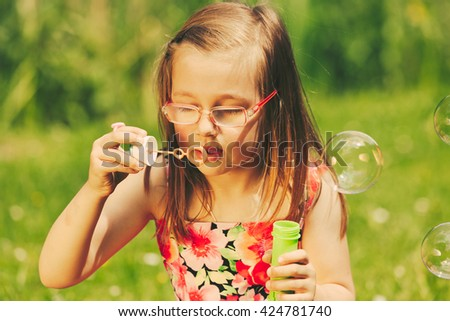 Little girl child blowing bubbles outdoor. Kid having fun in park. Happy and carefree childhood. Instagram filtered.